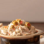 brown crock with olive dip on plate with pieces of pita