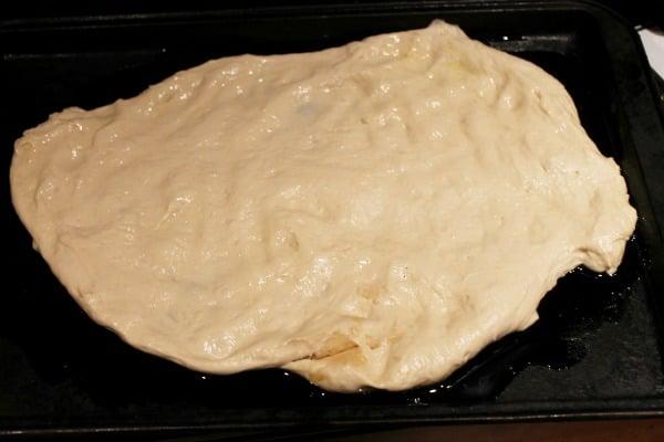 Flatten pizza dough into circle for homemade calzone