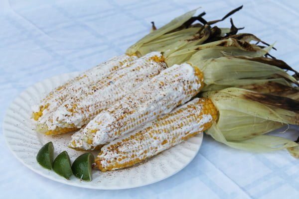 elotes, mexican corn on the cob with sour cream, parmesan, chili powder, and lime