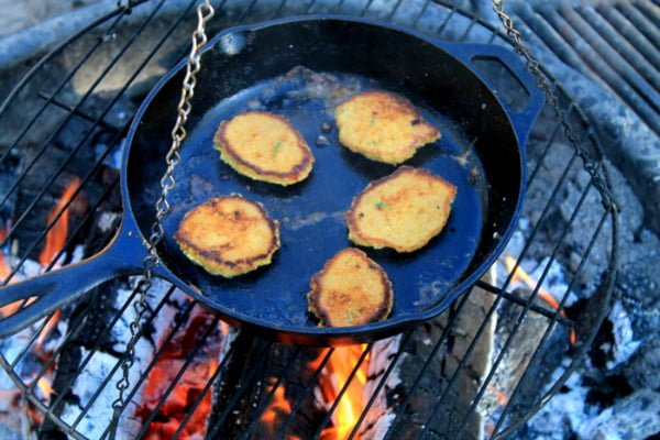 jalapeno cornbread cakes in cast iron pan over fire