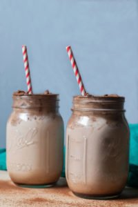 whipped chocolate milk in pint jars with red striped straw and teal cloth in background