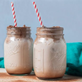 chocolate milk in 2 jars with chocolate whipped topping red striped straw and teal cloth background