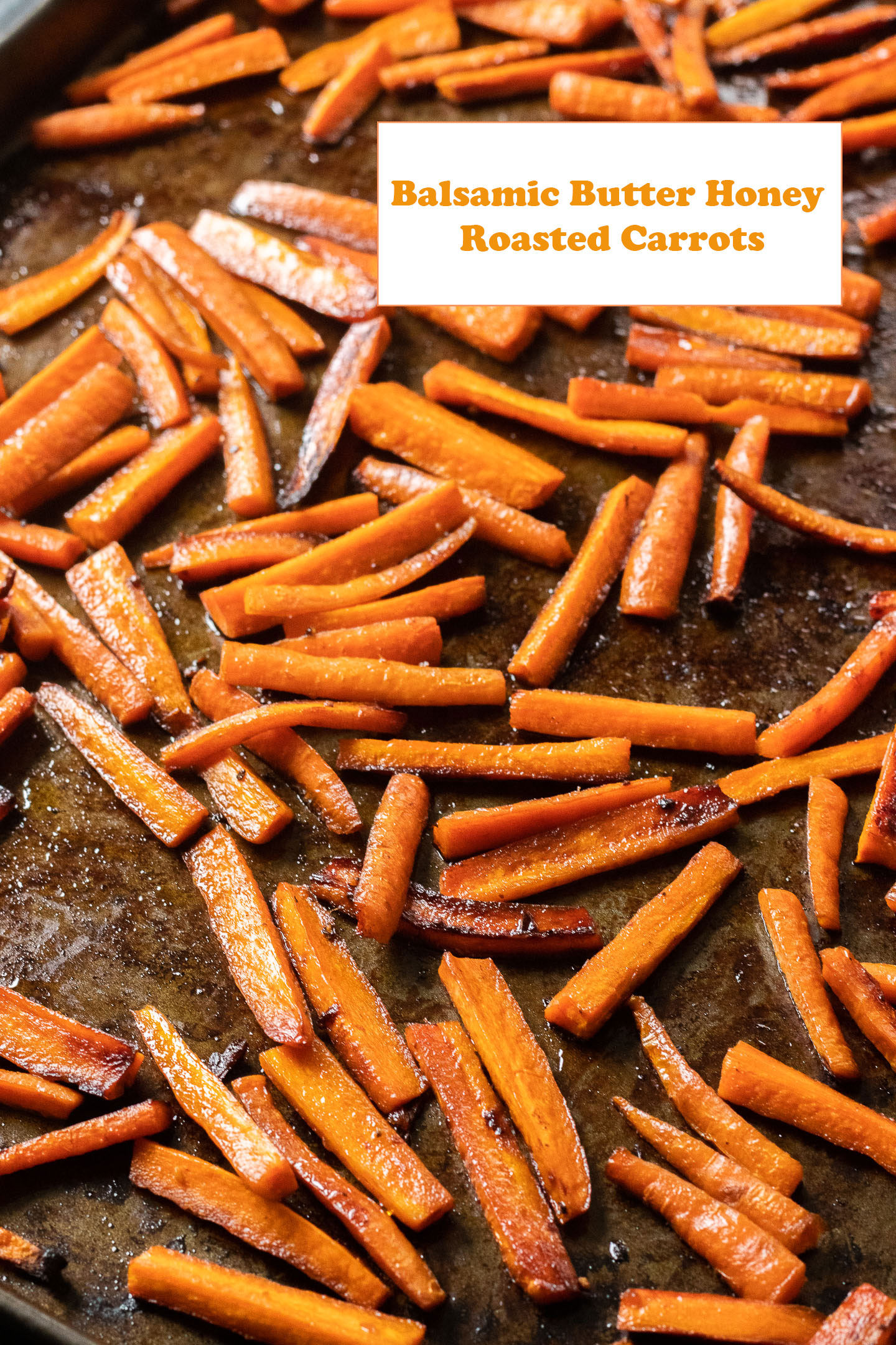 roasted carrot sticks on baking tray white rectangle in top right with orange lettering says balsamic butter honey roasted carrots