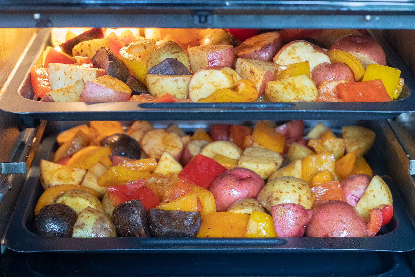 white, red, and purple potatoes and red and yellow bell peppers tossed with chili powder on air fryer oven trays
