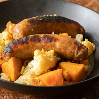 black bowl with 2 sausage links, cubed sweet potatoes and cauliflower florets