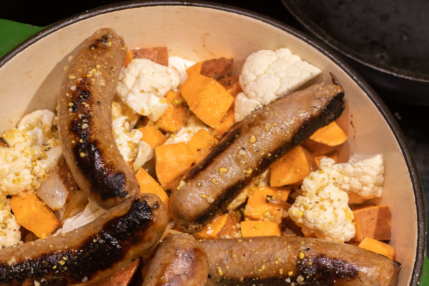 uncooked cubed sweet potatoes and cauliflower florets in enameled dutch oven with 5 browned sausage links on top