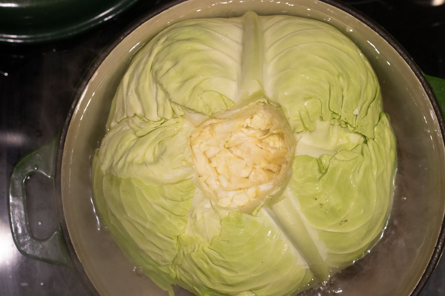 cored whole cabbage in pot of water