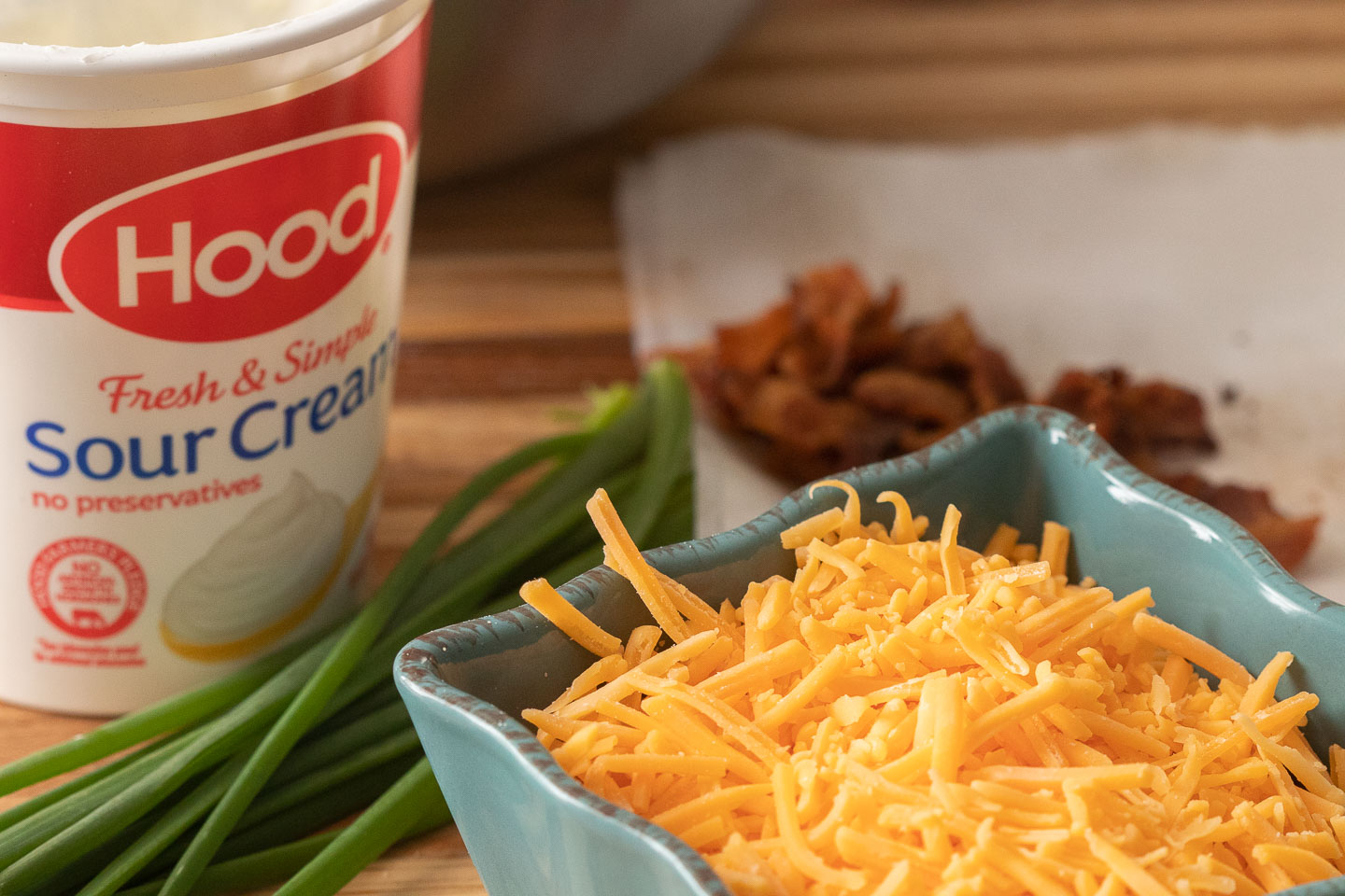 hood sour cream, chives, yellow cheddar in blue ceramic square bowl, bacon bits on napkin