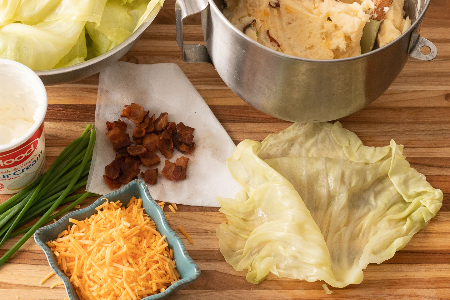 cutting board with cabbage leaf, yellow cheddar in blue ceramic square dish, chives, bacon bits on napkin, hood sour cream, mixing bowl with loaded mashed potatoes