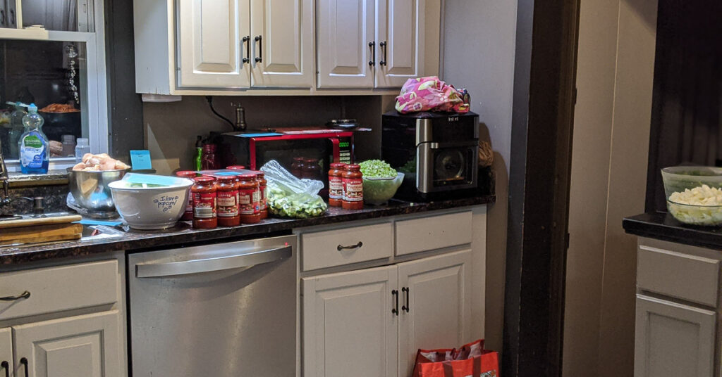 counter with cut up produce, jars of sauce